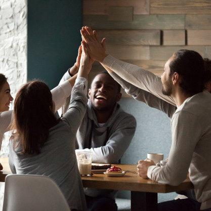 diversos-amigos-emocionados-entregando-high-five-juntos-reunion-cafe_1163-5146